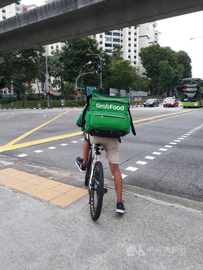 新加坡消費習慣面對防疫阻斷措施發生變化,餐飲業者也結合App訂餐等數位科技與物流做出改變,圖為送餐快遞員把熱騰騰美食或珍奶等餐飲配送到府。中央社記者黃自強新加坡攝 109年5月18日