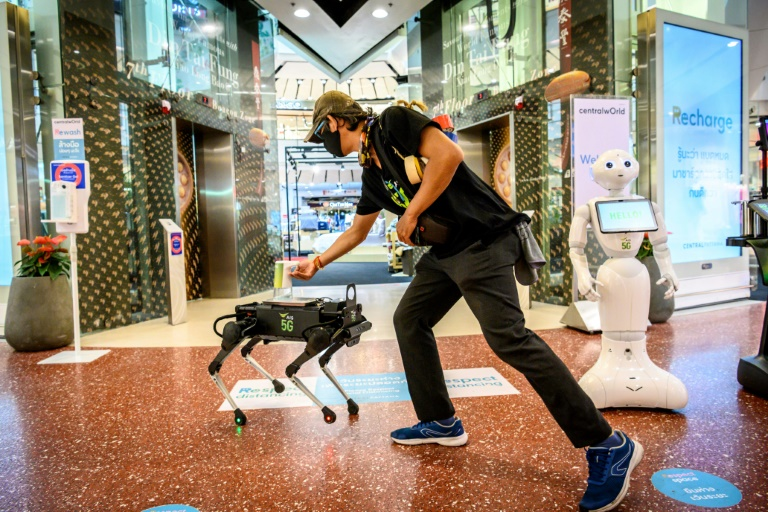 A 5G K9 robot distributes hand sanitiser to a visitor at a shopping mall in Bangkok. (AFP photo)