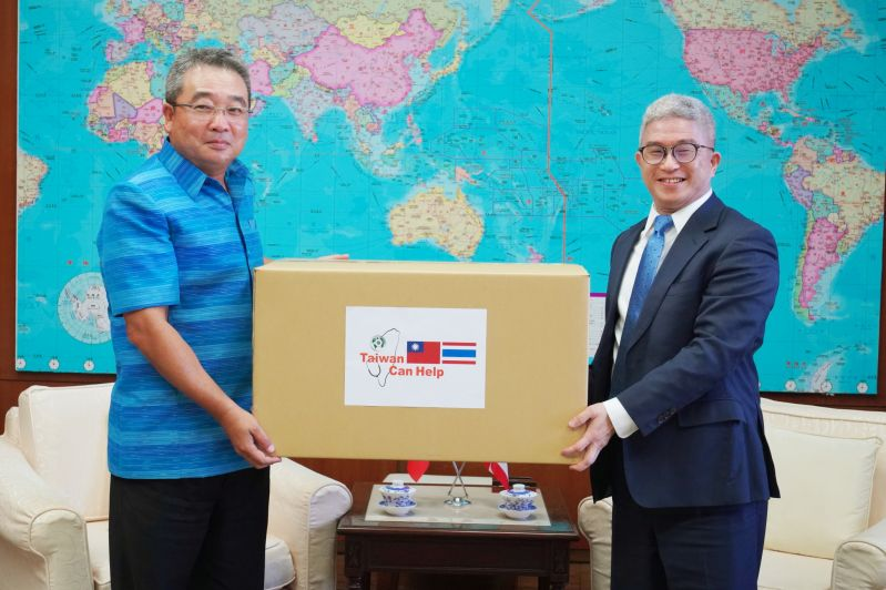 Deputy Foreign Minister Hsu Szu-chien (right) and Executive Director of Thailand Trade and Economic Office Thongchai Chasawath hold a box of surgical masks April 20 at MOFA headquarters in Taipei City. (MOFA)